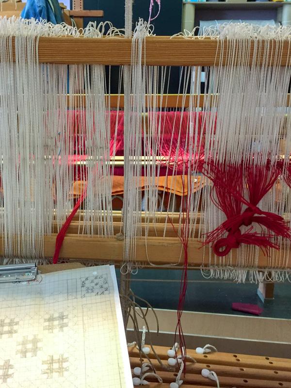 Die Kettfäden für das rote Parament werden Faden für Faden eingezogen