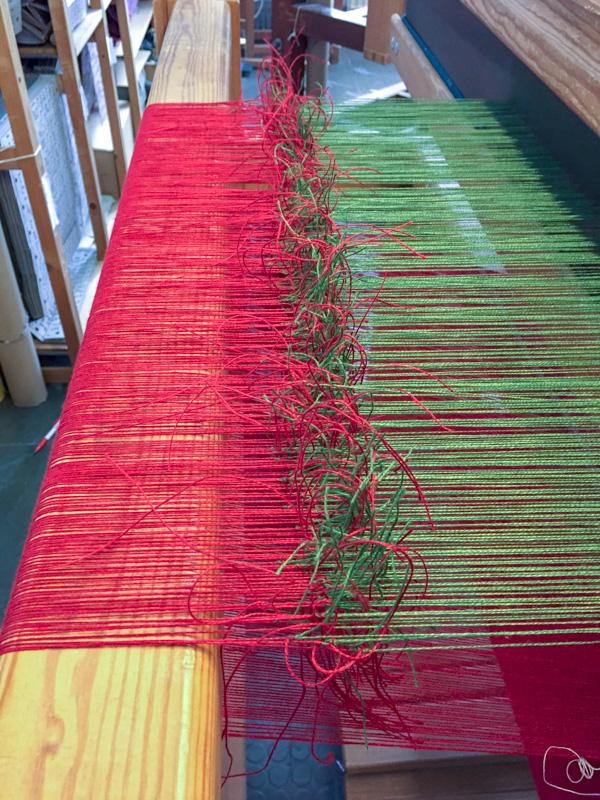 Die Kettfäden für das grüne Parament wurden an die roten Kettfäden angeknotet und durchgezogen